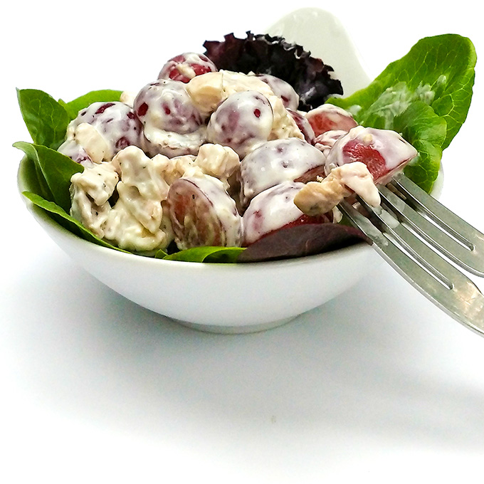 Chicken salad with grapes served over greens in a bowl